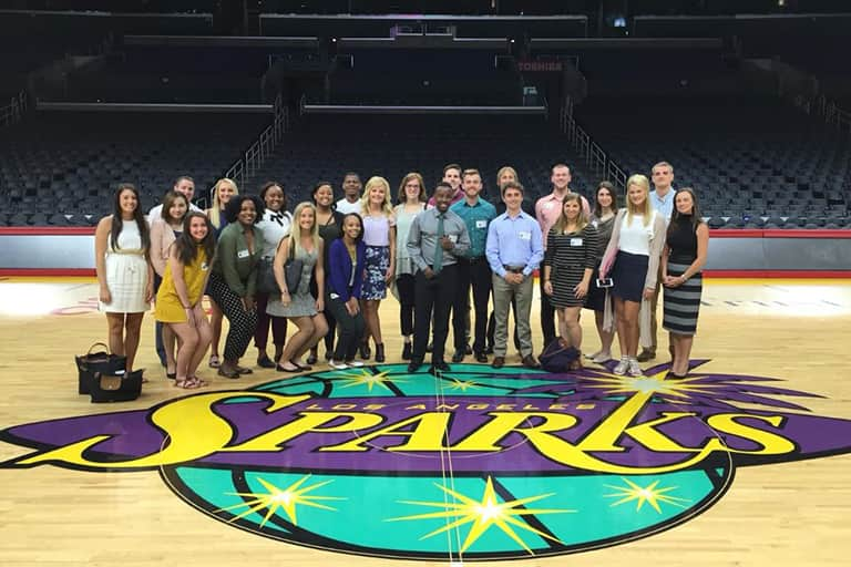 Students in the Los Angeles Study Away class standing together for a group shot in center court of the LA Sparks basketball arena.